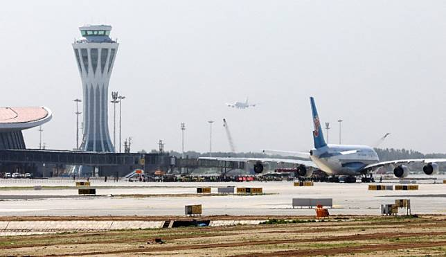 A plane lands in the distance as another sits on the tarmac at the new Beijing Daxing International Airport in Beijing on May 13, 2019. Chinese airlines conducted test flights on May 13 at a new mega-airport set to become one of the busiest in the world after it opens later this year. The tests at Daxing International Airport involved four wide-body planes, including an Airbus A380 super-jumbo.