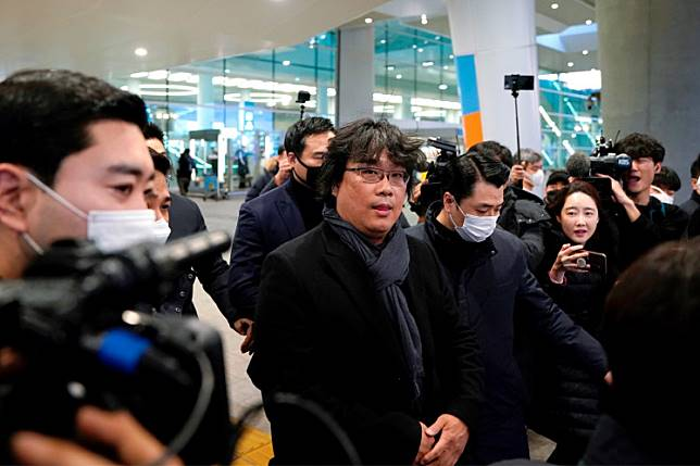 Director of four Oscar award-winning film 'Parasite' Bong Joon-ho is escorted by security personnel as he leaves Incheon International Airport, South Korea, on February 16, 2020.