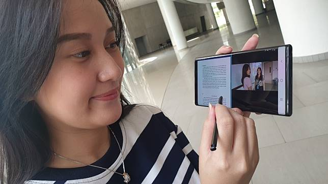 A model uses a Samsung Galaxy Note 10+ to edit photos and write articles.