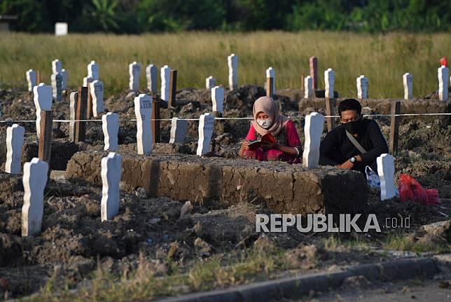 Peziarah berdoa di pemakaman khusus kasus COVID-19 di Tempat Pemakaman Umum (TPU) Keputih, Surabaya, Jawa Timur, Sabtu (16/5/2020). Pemkot Surabaya menyediakan lahan khusus di TPU Keputih untuk pasien yang meninggal dunia dan dimakamkan dengan protokol kesehatan COVID-19