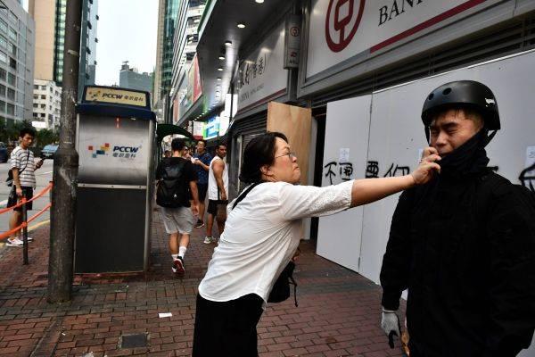 Seorang perempuan pro-Tiongkok mencoba melepas penutup muka seorang pengunjuk rasa di Hong Kong.