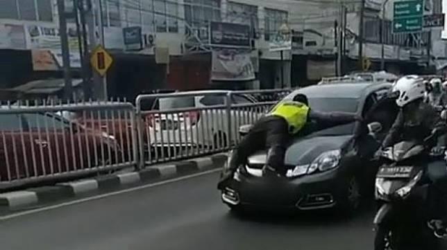 Bripka Eka Setiawan, anggota polisi lalu lintas menemplok di kap mobil SUV saat sedang melakukan razia tertib berlalu lintas. Bahkan, ia ikut terbawa di atas mobil jenis Honda Mobilio berwarna abu-abu yang melaju. [Facebook]