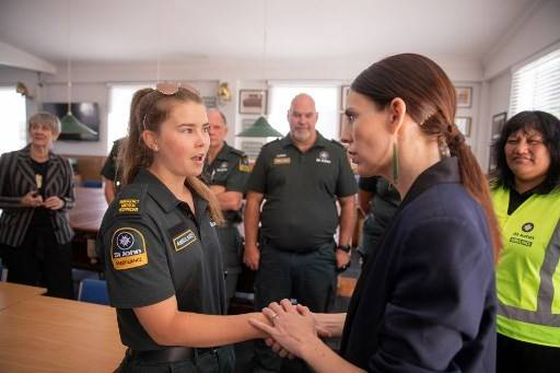 New Zealand's Prime Minister Jacinda Ardern (right) meets with a first responder from the St John's ambulance team that helped those injured in the White Island volcano eruption the day before, at the Whakatane Fire Station in Whakatane on Dec. 10, 2019. Survivors on Dec. 10 recounted dramatic escapes and tales of heroism when New Zealand's smoldering White Island volcano roared into life, amid