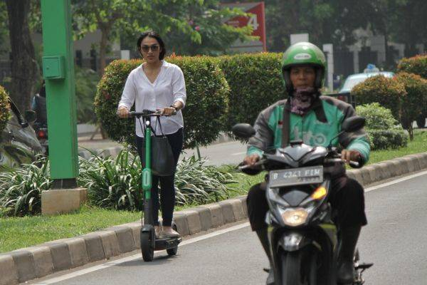 Sejumlah warga menggunakan skuter listrik Grab Wheels di Kawasan FX Sudirman, Jakarta Pusat, Rabu (13/11/2019).