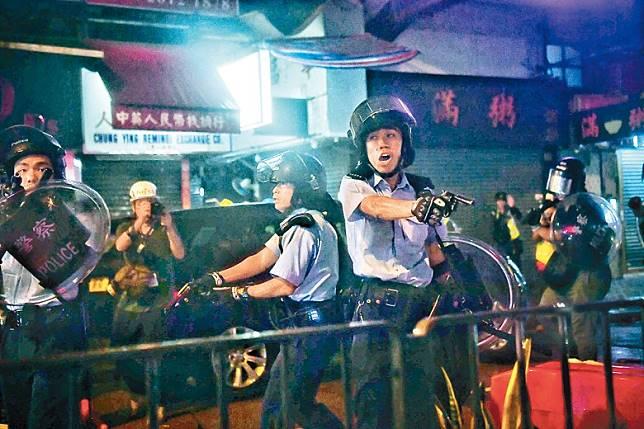 警員擎槍指嚇四周示威者。(法新社圖片)