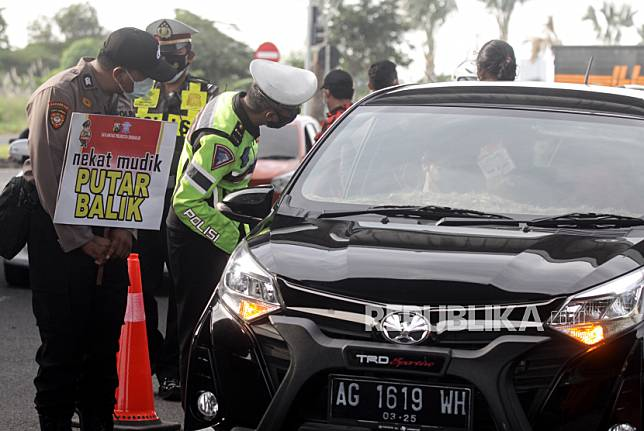 Petugas memeriksa kelengkapan surat dan KTP saat hari pertama penyekatan larangan mudik di perbatasan Kota Surabaya-Kabupaten Sidoarjo di Tambak Sumur, Sidoarjo, Jawa Timur, Kamis (6/5/2021).