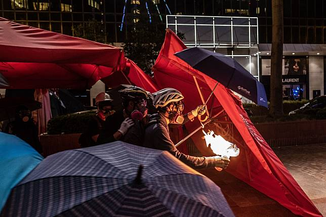 A demonstrator prepares to throw a petrol bomb towards riot police during a protest in the Tsim Sha Tsui district of Hong Kong on Nov. 18. Photographer: Justin Chin/Bloomberg