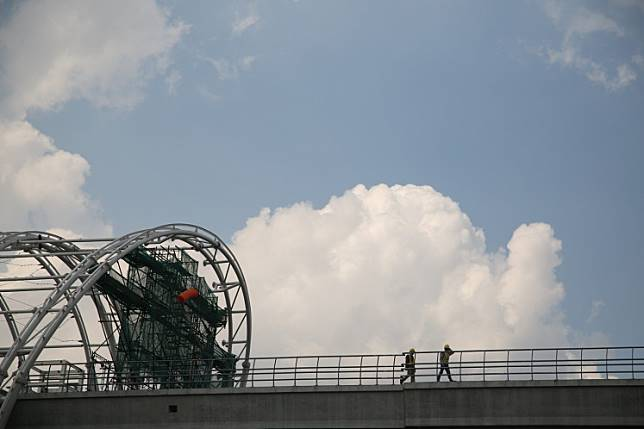 Two workers walk on the under-construction Greater Jakarta LRT in East Jakarta on May 28.