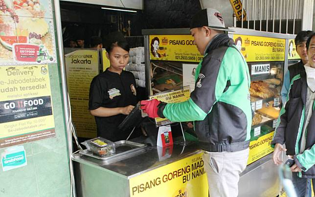 Personal shopper:  A Go-Jek driver shows his cellphone to a shopkeeper while buying fried banana for a customer in Tanjung Barat, West Jakarta.