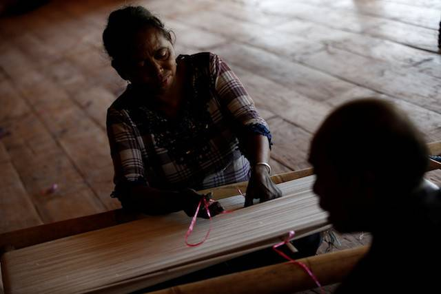 Maria Babang Noti, 51, and her husband Thomas Tay Ranjawali, 52, prepare to hand weave a traditional Sumba Ikat textile at Atma La Kanatang, their weaving house in Hamba Praing village, Kanatang district, East Sumba Regency, East Nusa Tenggara province, Indonesia, Feb. 23, 2020.But in the village of Hamba Praing in East Sumba, scores of horses and cattle have died in recent years as extreme drought withered the grass, leaving behind bones and carcasses scattered over the scrubby landscape.