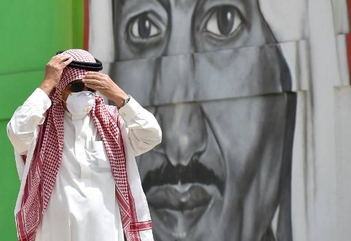 A Saudi man, wearing a protective mask as a precaution against COVID-19 coronavirus disease, adjusts his headgear while walking past a mural showing the face of King Salman bin Abdulaziz, along Tahlia street in the centre of the capital Riyadh on March 15, 2020.The kingdom's health ministry on Sunday said the death toll from the COVID-19 disease had doubled to eight as cumulative infections rose from 1,203 to 1,299 -- the highest in the Gulf region.