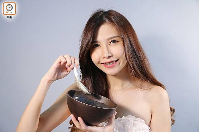模特兒吃芝麻糊將牙齒染黑,不少芝麻碎屑藏在牙縫中,以測試水牙線機的清潔力。(胡振文攝)