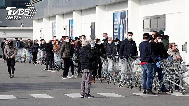 義大利政府緊急封閉12座城鎮後,超市外出現大批民眾排隊搶購物資。(圖/達志影像路透社)