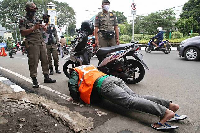A Public Order Agency (Satpol PP) officer takes a picture of a motorist made to do pushups as punishment for violating the large-scale social restrictions (PSBB) in Depok, West Java, on May 19. Punishments for offenders of PSBB measures range from pushups and singing the national anthem to sweeping the streets. JP/P.J. Leo