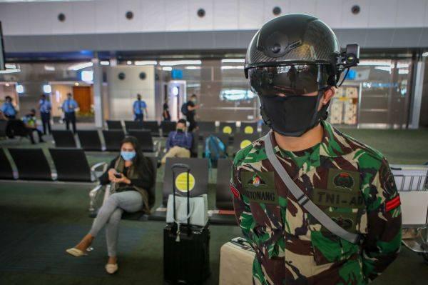 Personel TNI menggunakan helm pendeteksi suhu tubuh di Terminal 3 Bandara Internasional Soekarno Hatta, Tangerang, Banten