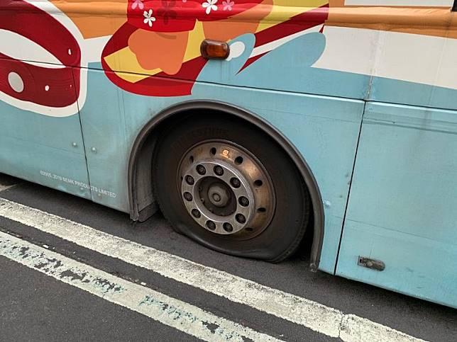 巴士車胎遭放氣。(陳嘉順攝)