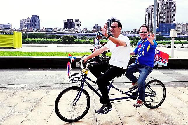 新北市長朱立倫和國民黨立委參選人林郁方9日在萬華馬場町紀念公園共乘輔選單車。( 圖 / 朱立倫辦公室提供 )