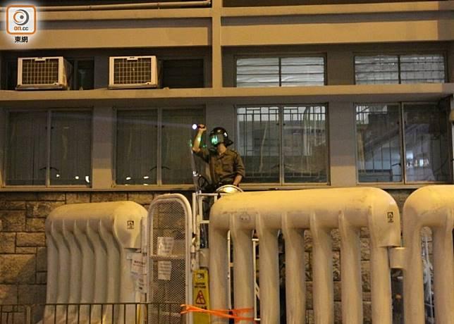 被照雷射光的防暴警員用強光反照示威者。(袁以諾攝)