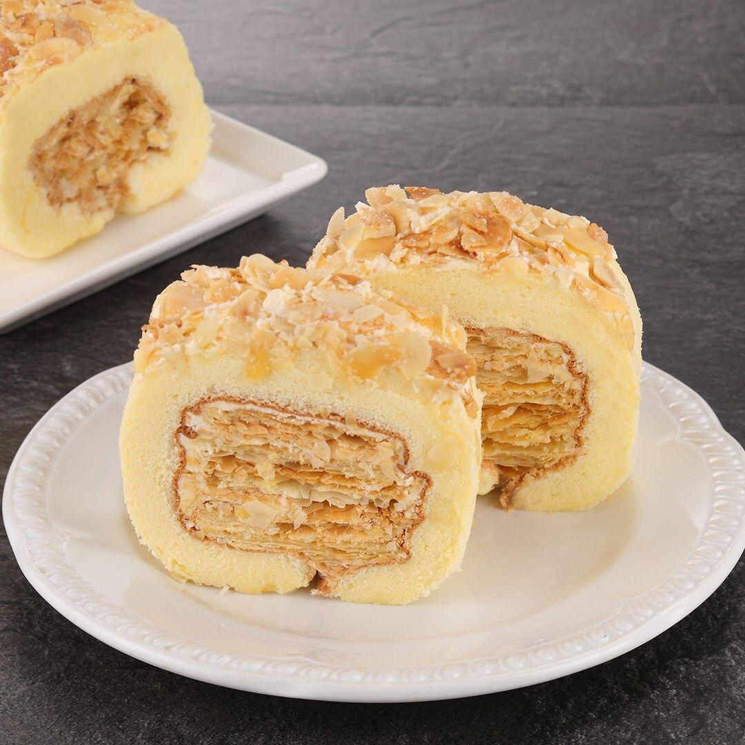 以特級奶油製成中間香酥的千層酥皮,複雜的層次中散發著淡淡的奶油香氣,一口咬下爽脆的口感證明它的不平凡。外層捲上綿密的戚風蛋糕,再灑上烤得香脆糖霜杏仁片,三種截然不同的口感立刻襲捲包覆你的味蕾,不甜不膩