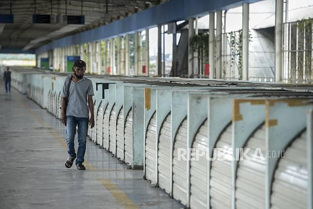 Seorang warga melintas di dekat pertokoan yang tutup di kawasan Tanah Abang, Jakarta, Senin (25/5). Hari kedua Hari Raya Idul Fitri 1441 Hijriyah dan masih berlakunya masa Pembatasan Sosial Berskala Besar (PSBB) membuat Pasar Tanah Abang sepi dari aktivitas perdagangan