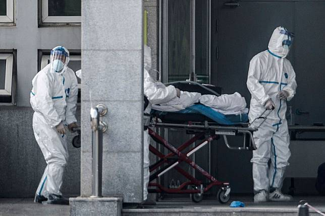 Medical staff members carry a patient into the Jinyintan Hospital, where patients infected by a mysterious SARS-like virus are being treated, in Wuhan in China's central Hubei province on Jan. 18.