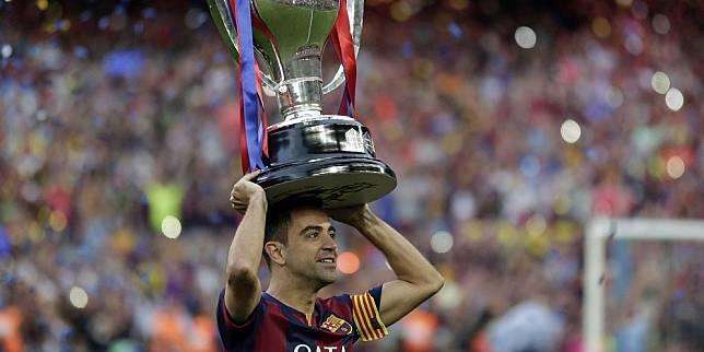 Gelandang Barcelona Xavi Hernandez mengangkat trofi La Liga di Camp Nou setelah Barcelona menjadi juara, 23 Mei 2015. (c) AP Photo
