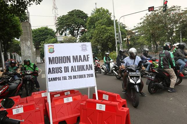 Motorists take U-turns at a road closure traffic notice at a junction before the Senayan legislative complex in Central Jakarta. The roads behind the House of Representatives were closed on Friday ahead of the presidential inauguration scheduled on Sunday.
