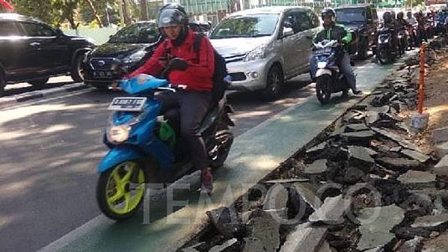 Warga melintas di samping jalur sepeda yang dibongkar di Jalan Pangeran Diponegoro, Cikini, Jakarta, Selasa, 19 November 2019. Jalur sepeda di kawasan itu bagian dari jalur sepeda fase pertama yang diresmikan Gubernur Anies Baswedan pada September lalu. TEMPO/Imam Hamdi