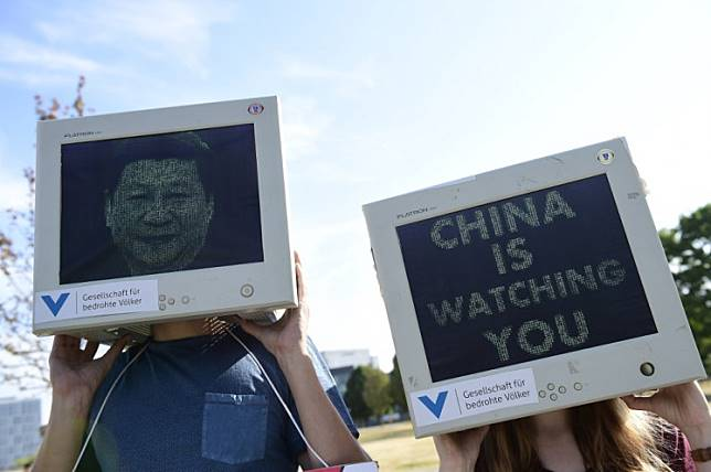 Activists of the 'Society for Threatened Peoples' (Gesellschaft fuer bedrohte Voelker) demonstrate wearing computer monitors with a portrait of Chinese President Xi Jinping and the words 'China is watching you' during a demonstration next to the Chancellery in Berlin on July 9, 2018, prior a meeting between German Chancellor and Chinese Premier. German Chancellor Angela Merkel holds talks on July 09, 2018 with Chinese Premier Li Keqiang amid fears of a spiralling global trade war touched off by new US tariffs.