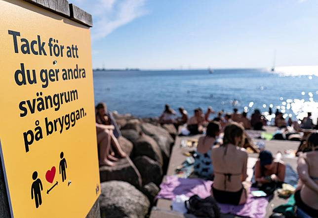 An information sign recommends people to keep social distance due to the COVID-19 pandemic, where people sunbathe and swim at a bathing jetty in Malmo, Sweden, on June 25, 2020.Sweden's daily tally of new COVID-19 cases fell to its lowest since late May on Tuesday, a sharp reversal from June when expanded testing fuelled record numbers in a country that drew global attention for its rejection of a lockdown.