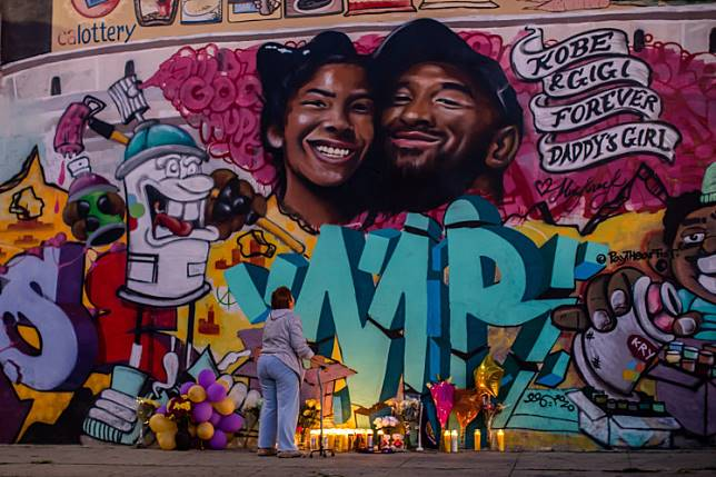 A woman looks at a mural by the artists Muck Rock and Mr79lts showing Kobe Bryant and his daughter Gianna Bryant, who were killed with seven others in a helicopter crash on January 26, in Los Angeles on January 27, 2020.