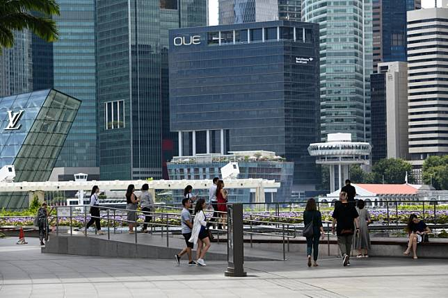 This photograph taken on February 18, 2020 shows people walking near commercial buildings in the central business district in Singapore.