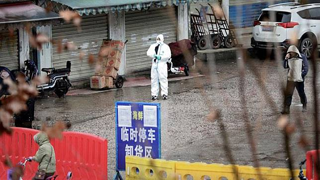 A worker in a protective suit is seen at the closed seafood market in Wuhan, Hubei province, China January 10, 2020. The seafood market is linked to the outbreak of the pneumonia caused by the new strain of coronavirus, but some patients diagnosed with the new coronavirus deny exposure to this market. REUTERS/Stringer
