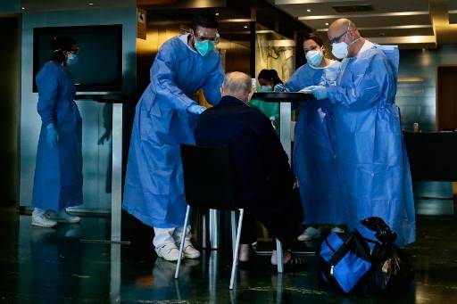 Healthcare workers attend to a COVID-19 patient upon his arrival at the Hotel Melia Barcelona Sarria on April 2, 2020 in Barcelona, as the hotel was transformed into a medical structure to treat the least serious cases amid the outbreak caused by the novel coronavirus. The coronavirus death toll in Spain surged past 10,000 after a record 950 deaths in 24 hours, with the number of confirmed cases passing the 110,000 mark, the government said.
