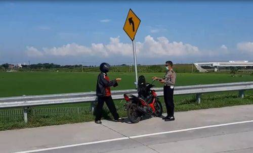 Petugas Satlantas Polres Ngawi menghentikan pengendara motor yang nekat masuk tol. (foto/metrotv)