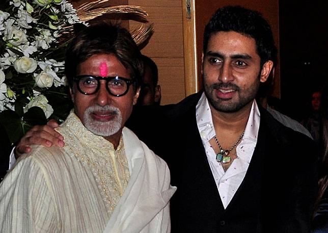Bollywood actors Amitabh Bachchan (left) and his son Abhishek Bachchan pose for a picture during a party of a new Bollywood production company in Mumbai on February 28, 2010.