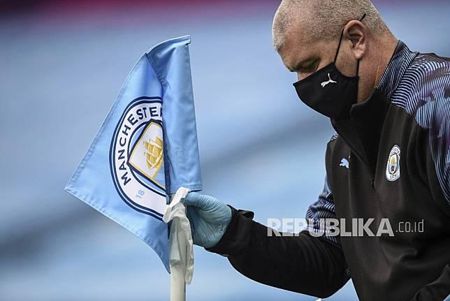 Seorang staf Manchester City mendisinfeksi tiang sudut pada pertandingan sepak bola Liga Primer Inggris  antara Manchester City dan Newcastle di Stadion Ethiopia di Manchester, Inggris, Rabu (8/7/2020).