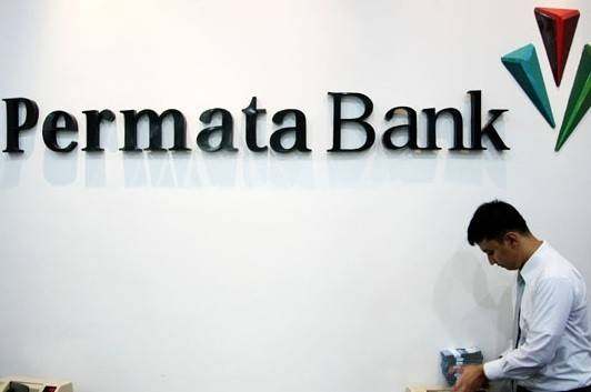 A man walks past the logo of Bank Permata at a branch office of the lender in Jakarta.