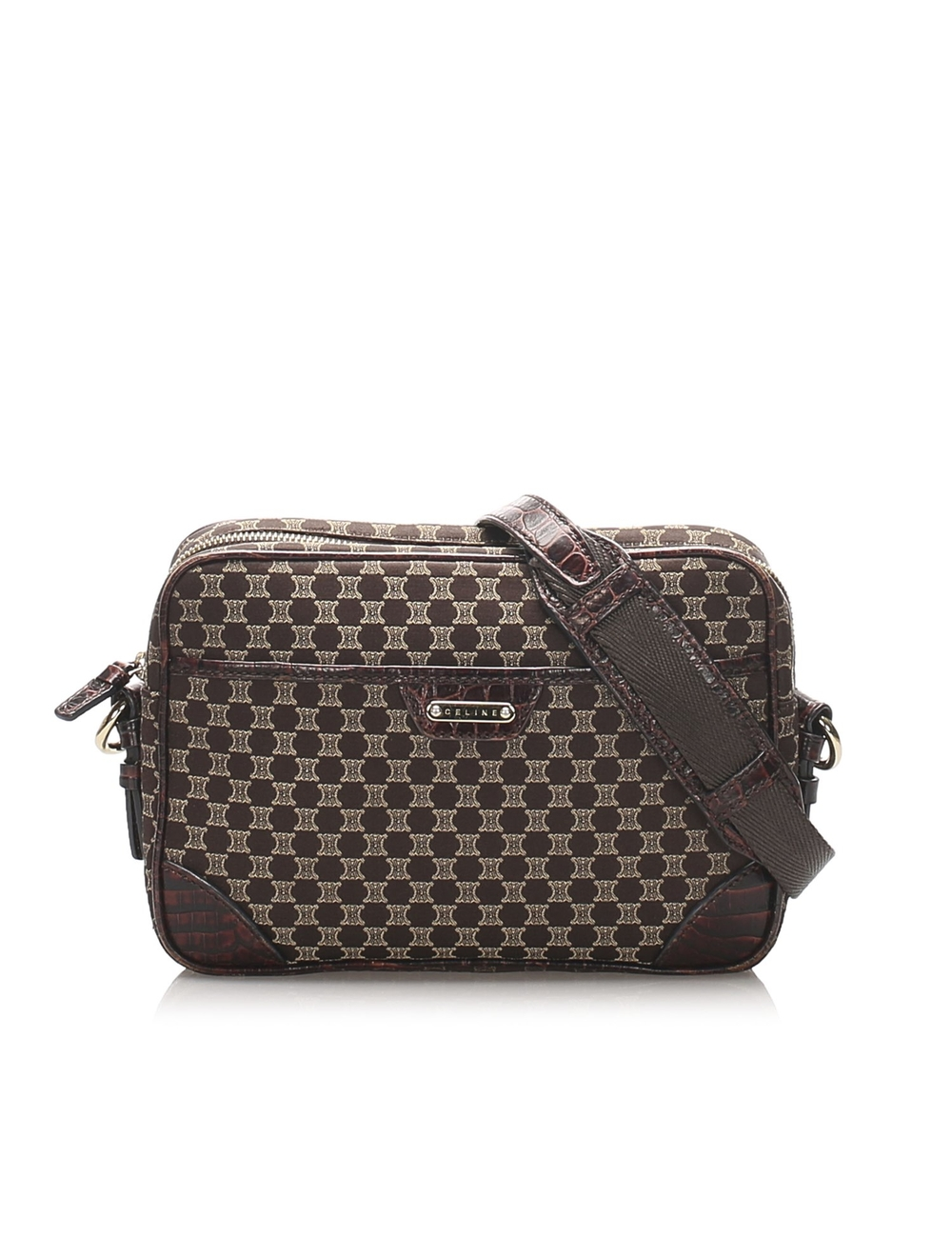 This crossbody bag features a canvas body, a front exterior slip pocket, a flat leather strap, a top