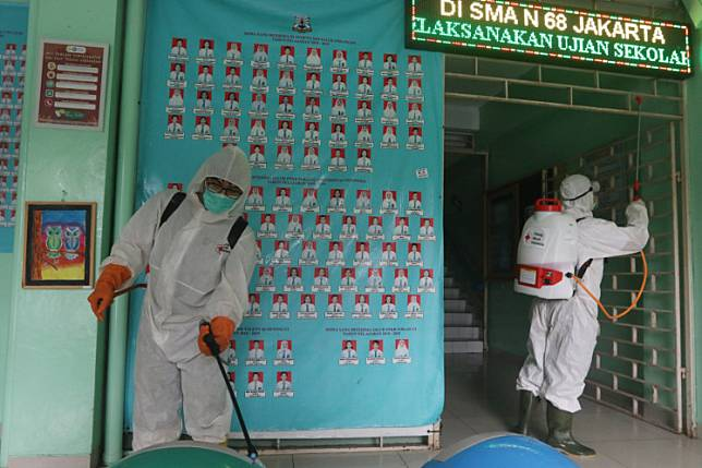 Indonesian Red Cross (PMI) officers spray disinfectant in 68 Jakarta state high school on March 16 to prevent the spread of COVID-19.