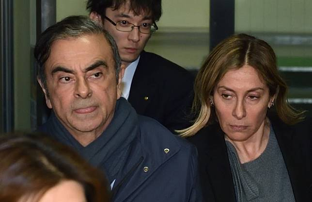 This picture taken on April 3, 2019 shows former Nissan Chairman Carlos Ghosn (left) and his wife Carole (right) leave the office of his lawyer Junichiro Hironaka in Tokyo. Former Nissan boss Carlos Ghosn will remain in custody until at least April 14, a Japanese court ruled on April 5, 2019, as prosecutors quiz him over fresh allegations of financial misconduct.