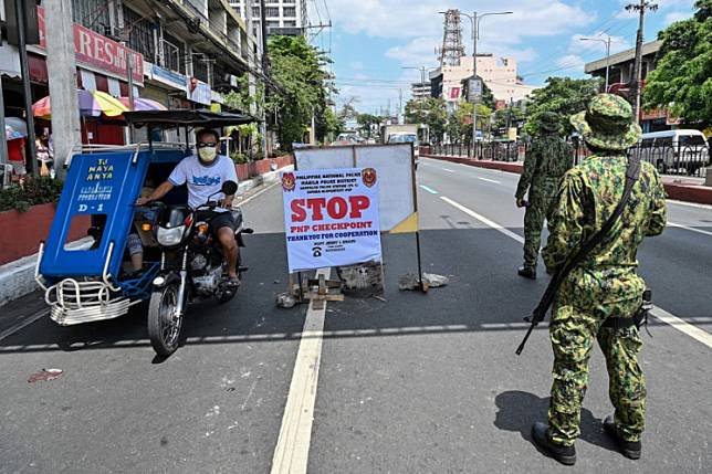 Philippine police man a checkpoint on the border between Quezon city and Manila districts on March 18, 2020, as the government imposed measures to curb the spread of the COVID-19 coronavirus.Philippines President Rodrigo Duterte said he's inclined to extend a lockdown of more than half the country's population on its main island until April 30 to further stem the coronavirus outbreak.