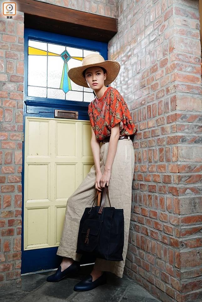 草帽、橙色圖案上衣、杏色長褲、黑色布袋、黑色Slip On皮鞋。(方偉堅攝)