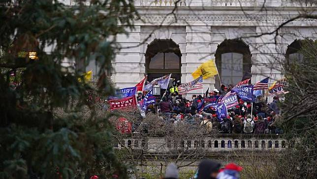 Massa pendukung Presiden Amerika Serikat Donald Trump tiba di pintu masuk samping Capitol Hill, Washington, Amerika Serikat, Rabu (6/1/2021). Sejumlah polisi DC pun jadi korban, mereka dibawa ke rumah sakit setelah terkena semprotan merica. (AP Photo/Julio Cortez)
