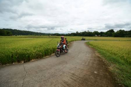 Villagers ride motorcycle along the newly repaired road in Minahasa Baji Village, South Sulawesi on Nov. 29.Indonesia plans to mobilize volunteers to fight the spread of coronavirus in coastal villages and the vast hinterlands of the archipelago with part of a $4.4 billion rural budget to be used to fund the initiative.