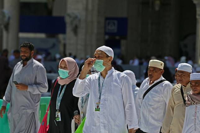 Muslim pilgrims wear masks at the Grand Mosque in Saudi Arabia's holy city of Mecca on February 27, 2020. - Saudi Arabia suspended visas for visits to Islam's holiest sites for the