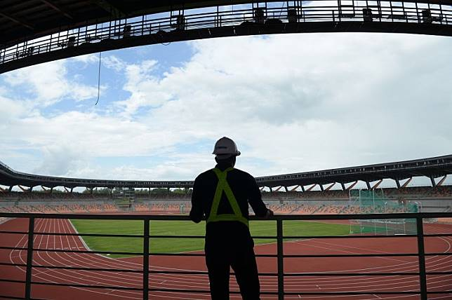 A worker stands inside the athletics stadium for this year's Southeast (SEA) Asian Games in New Clark City in Capas town, Tarlac province, north of Manila on July 19. The SEA Games will be held from Nov. 30 to Dec. 11.