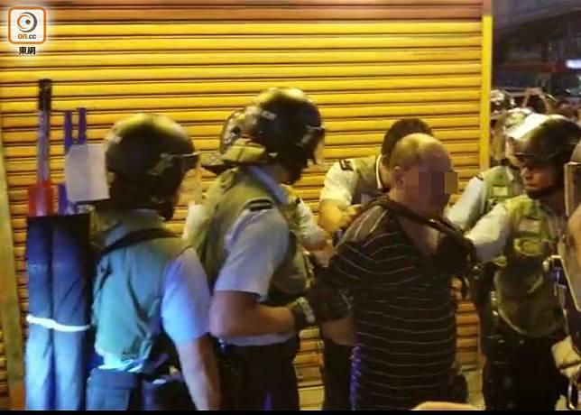 弼街一名男子涉嫌在公眾地方行為不檢被警員帶走。(劉志城攝)