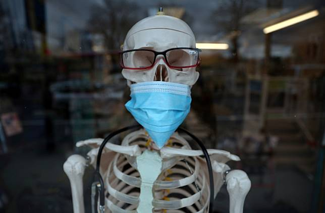 A skeleton mannequin wearing a protective mask is seen in the window of a medical equipment supply store in south London, Britain February 26, 2020.