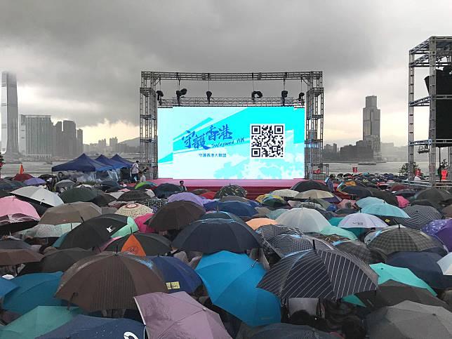 參加市民舉起雨傘。